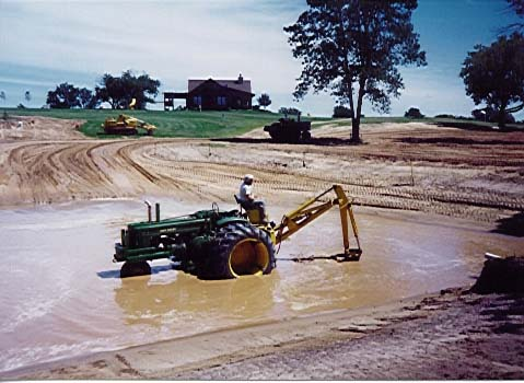 JD A with Backhoe in Pond